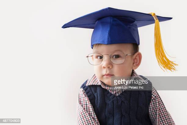 Hispanic toddler wearing mortar board