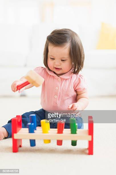 Hispanic toddler with Down syndrome playing