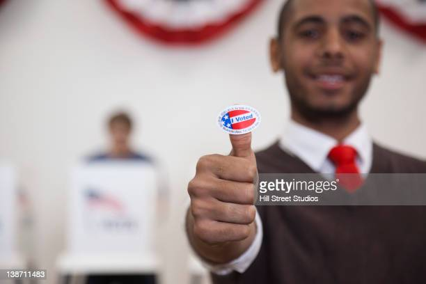 hispanic voter holding an i voted sticker in polling place - i voted sticker - fotografias e filmes do acervo