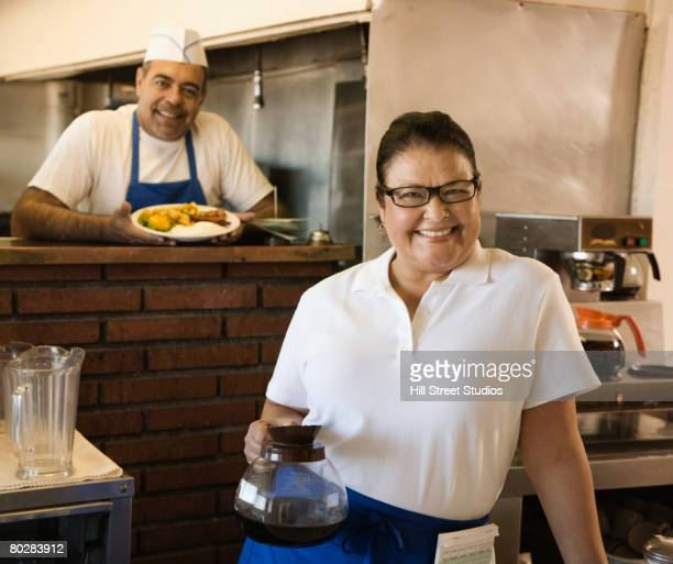 Hispanic waitress and cook in diner