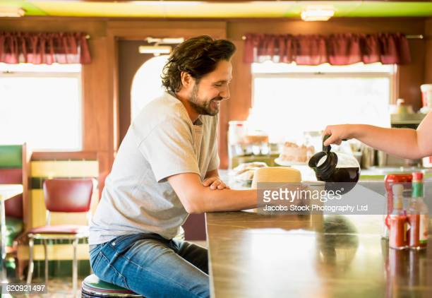 Hispanic waitress pouring coffee for customer in diner