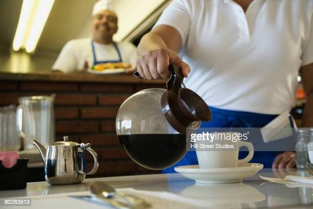 hispanic waitress pouring coffee - diner stock pictures, royalty-free photos & images