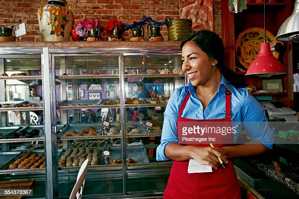hispanic waitress taking orders in bakery - waitress stock pictures, royalty-free photos & images