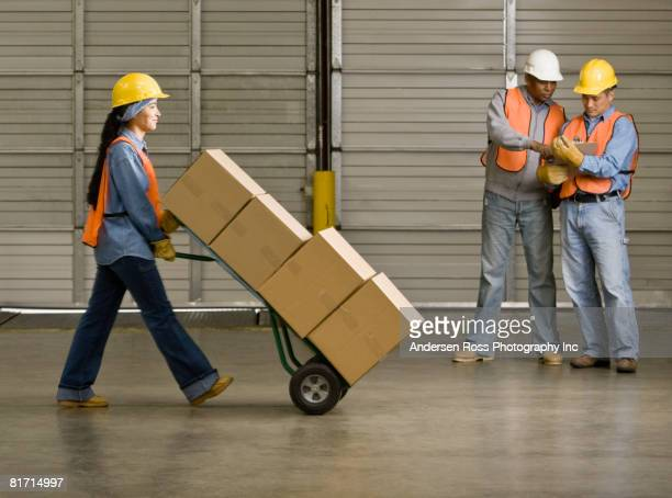 Hispanic warehouse worker pushing boxes on hand truck