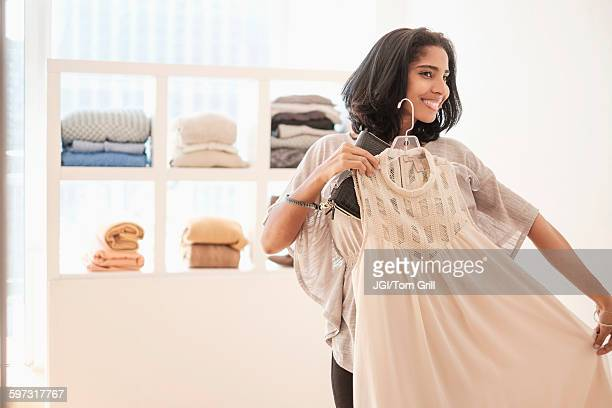 hispanic woman admiring clothing in store - garment stock pictures, royalty-free photos & images