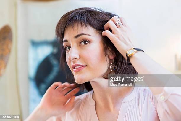 Hispanic woman admiring hair in mirror