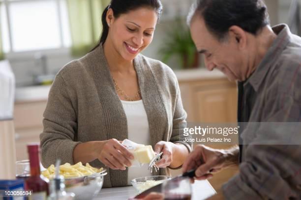 Hispanic woman and father preparing dinner