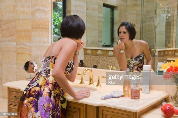 Hispanic woman applying lipstick in bathroom mirror