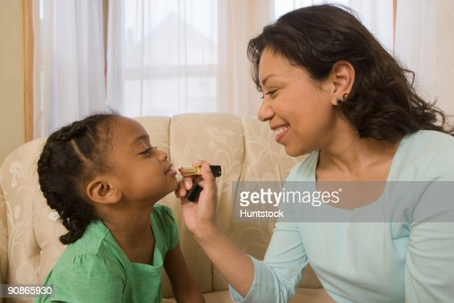 Hispanic Woman Applying Lipstick On Her Daughters Lips