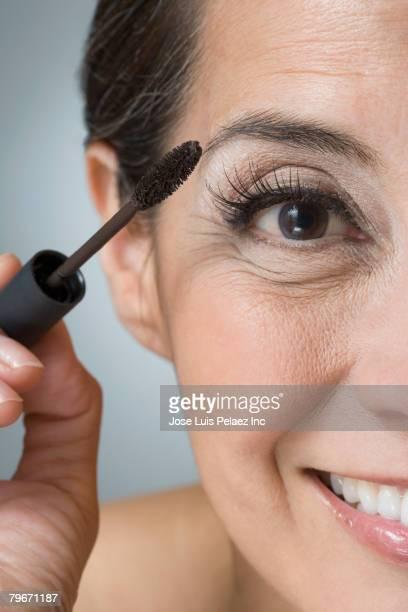 Hispanic woman applying mascara