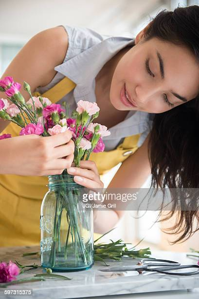 Hispanic woman arranging bouquet of flowers
