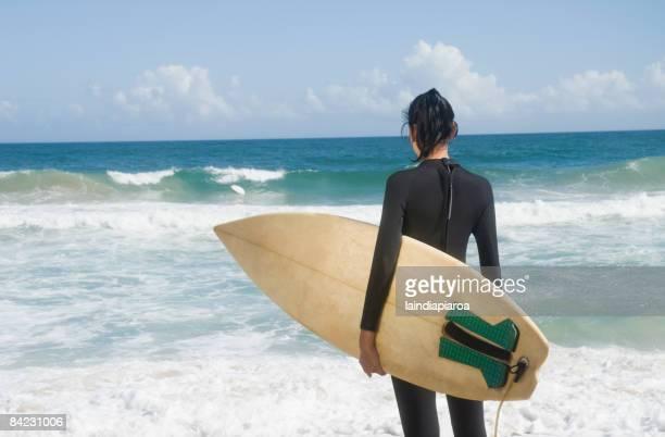 Hispanic woman at beach with surfboard