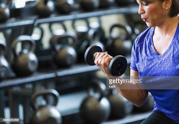 Hispanic woman at gym lifting dumbbell