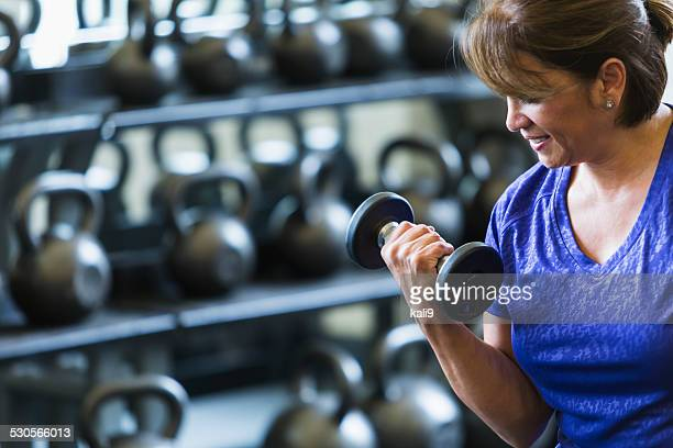 hispanic woman at gym lifting dumbbell - hand weight stock pictures, royalty-free photos & images