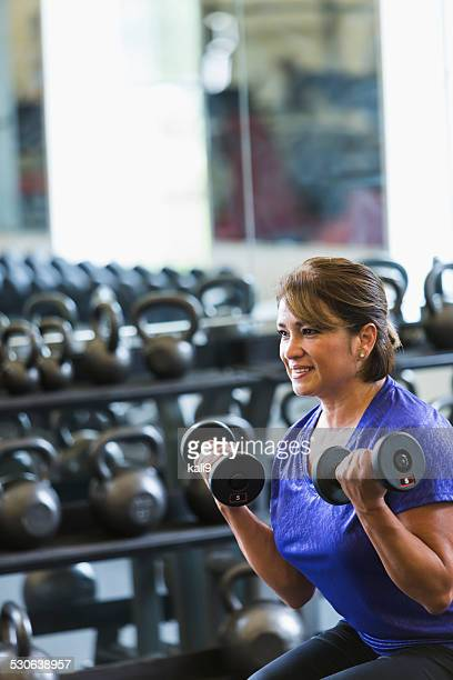 Hispanic woman at gym lifting dumbbells
