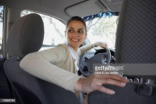 Hispanic woman backing up car