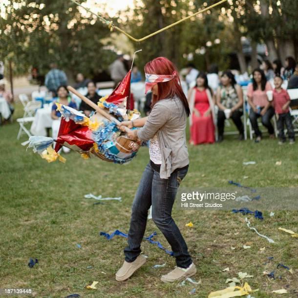 hispanic woman batting at pinata - pinata stock pictures, royalty-free photos & images