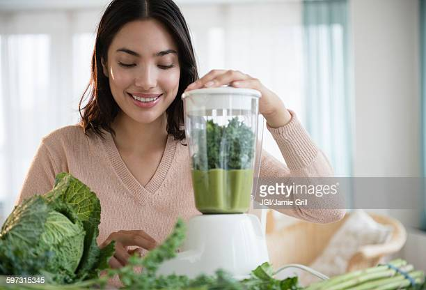 Hispanic woman blending healthy smoothie