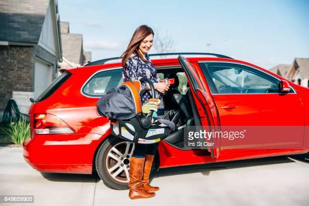 Hispanic woman carrying baby in car seat
