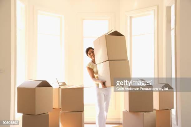 hispanic woman carrying cardboard boxes - oggetti pesanti foto e immagini stock