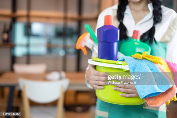 hispanic woman carrying cleaning supplies - メイド ストックフォトと画像
