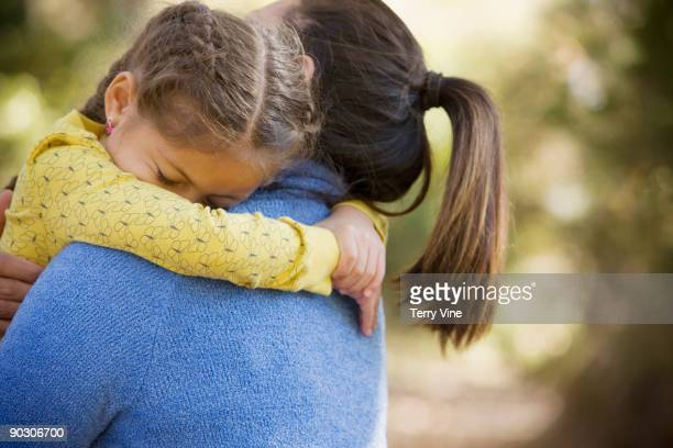 Hispanic woman carrying daughter