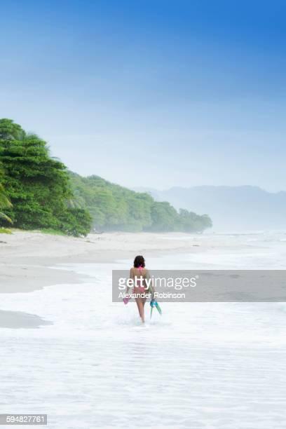 Hispanic woman carrying fins on beach