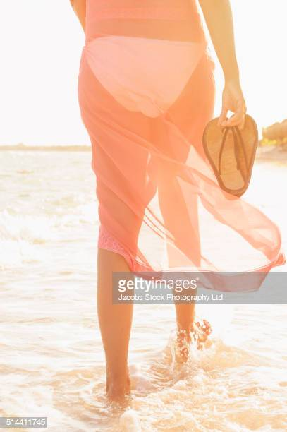 Hispanic woman carrying flip flops in waves on beach
