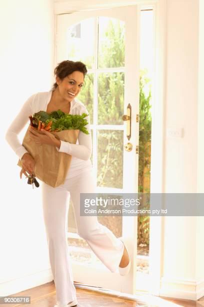 Hispanic woman carrying groceries indoors