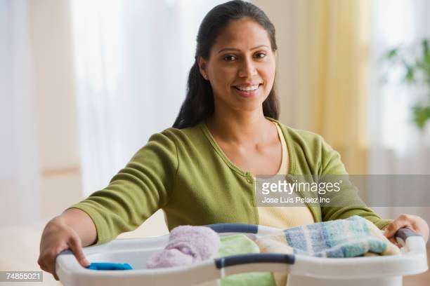 Hispanic woman carrying laundry basket