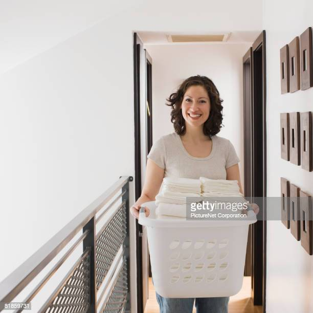 Hispanic woman carrying laundry basket
