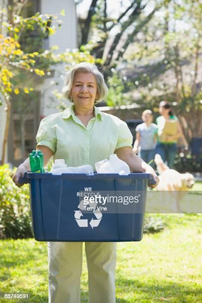 hispanic woman carrying recycling bin - mujeres de mediana edad fotografías e imágenes de stock