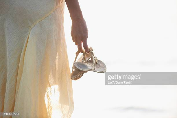 hispanic woman carrying sandals - open toe stock pictures, royalty-free photos & images