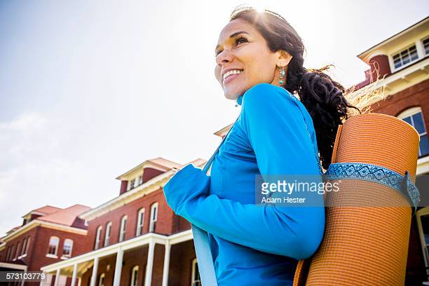 Hispanic woman carrying yoga mat outdoors