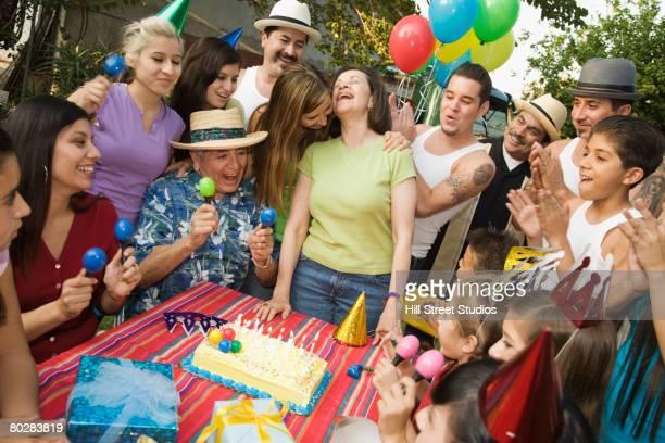 Hispanic woman celebrating birthday with family