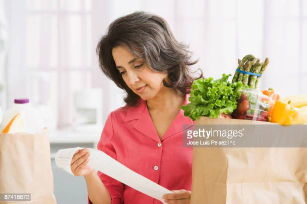 Hispanic woman checking grocery receipt