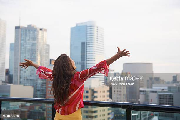 Hispanic woman cheering on urban rooftop