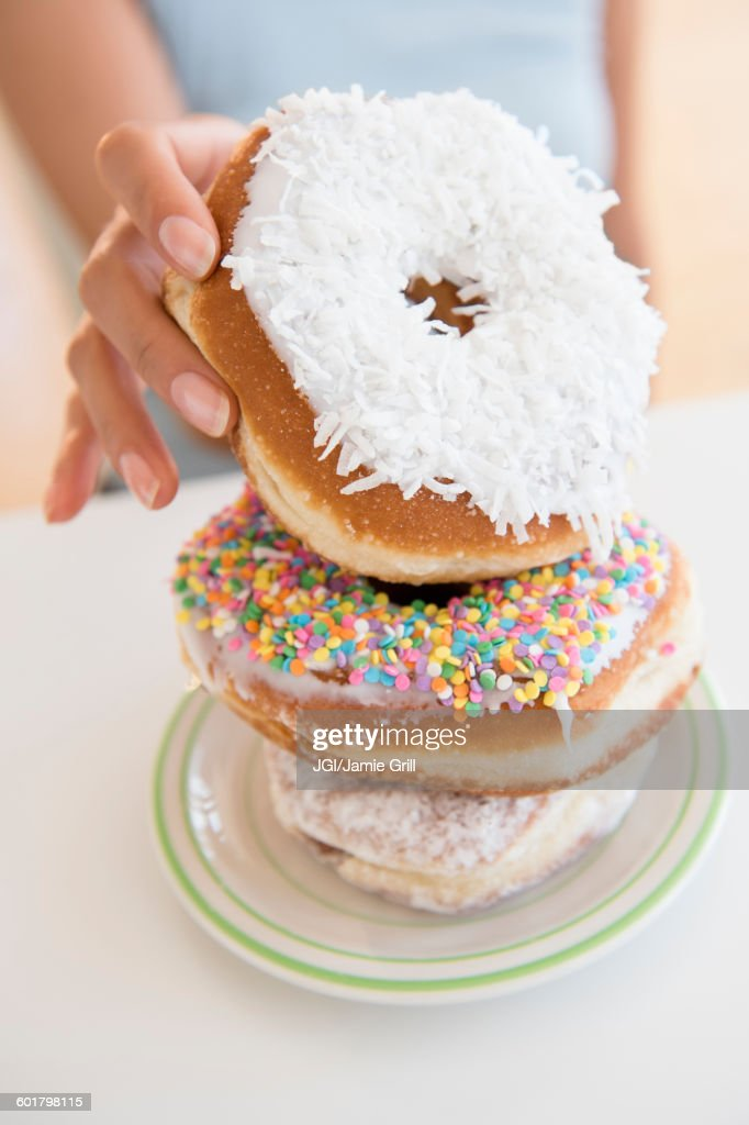 Hispanic woman choosing donut : Stock Photo