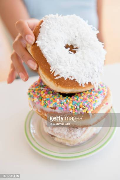 hispanic woman choosing donut - mid section stock photos and pictures