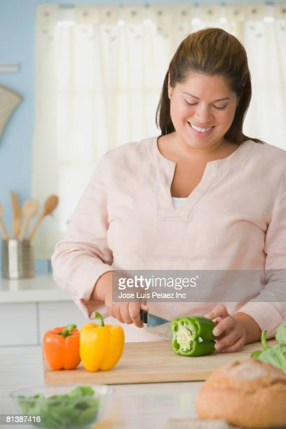 hispanic woman chopping bell peppers - fat nutrient stock pictures, royalty-free photos & images