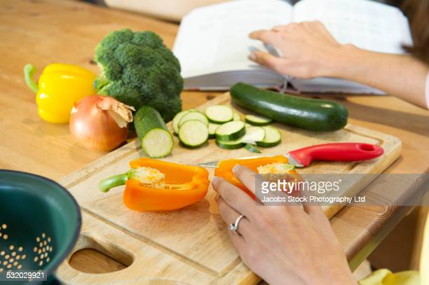 Hispanic woman chopping vegetables at kitchen table