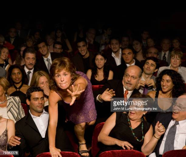 Hispanic woman climbing over theatre seats