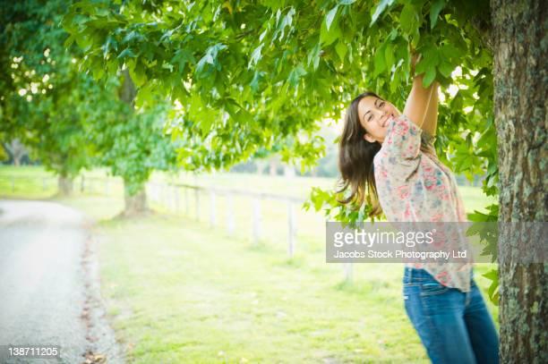 Hispanic woman climbing tree