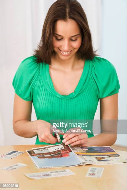 hispanic woman clipping coupons - coupon stock photos and pictures