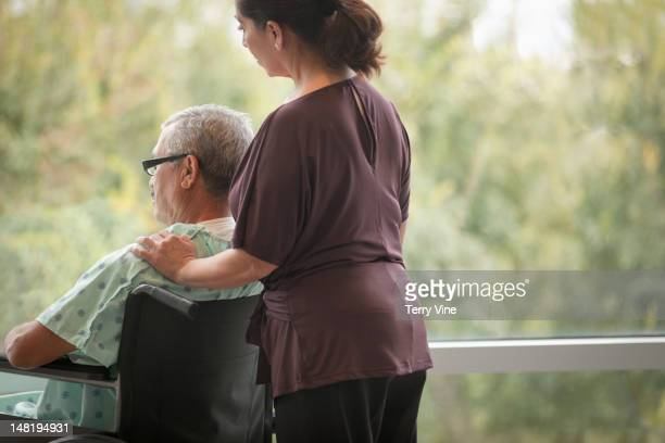 Hispanic woman comforting man in wheelchair