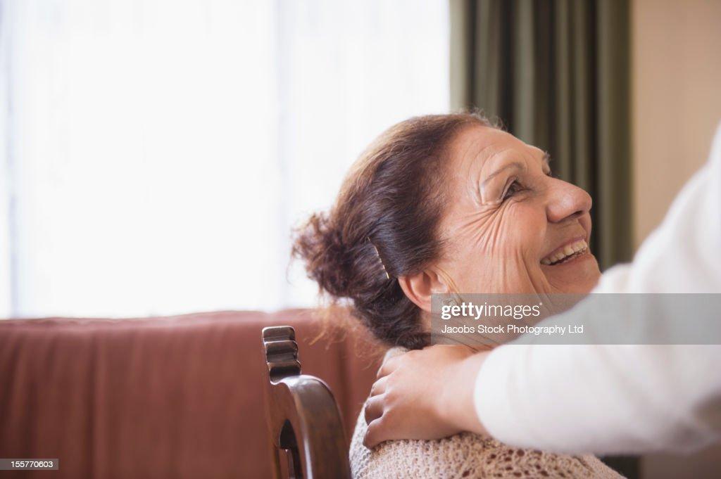 Hispanic woman comforting senior woman : Stock Photo