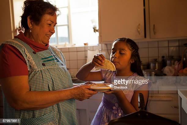 hispanic woman cooking for granddaughter in kitchen - chubby granny fotografías e imágenes de stock