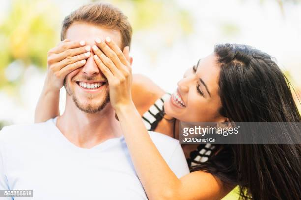 Hispanic woman covering eyes of boyfriend outdoors