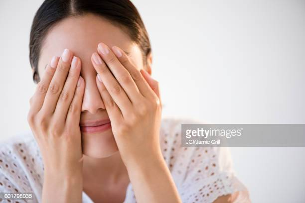Hispanic woman covering her eyes