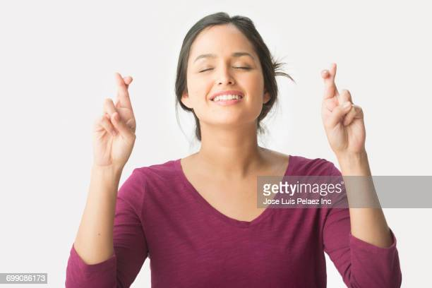 Hispanic woman crossing fingers with eyes closed